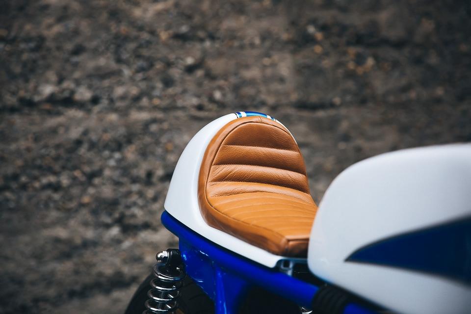 C'est dans les rues de Portland, USA, et ses collines environnantes, que vous pourrez voir ce superbe carénage fait sur mesure et à la main, autour ce cette non moins superbe structure tubulaire bleue. La selle, le réservoir, et la bulle sont empruntées à la mythique version sport TR500 de Suz'. Dans l'esprit d'authenticité, notre ami américain a choisi de conserver le simple disque avant, et de recréer au mieux une moto d'époque. Le moins que l'on puisse dire, c'est que le résultat est impressionnant ! Ce qui explique sans doute qu'il ait préféré garder sa mob' plutôt que de la vendre. Mais s'il change d'avis, je suis preneur !